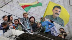 Syrian Kurds waving a Kurdish flag and image of Abdullah Ocalan in Aleppo