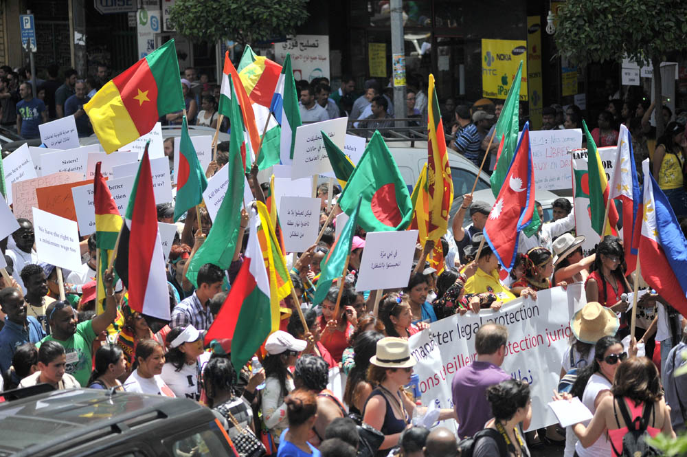 Migrant workers holding their national flags during the march