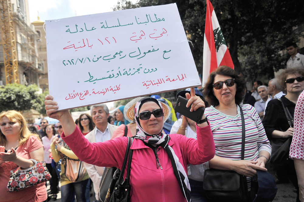 Sign held by a protester from the engineering department at the Lebanese University: Our demand is to have a fair wage scale, and it is 121%,with a retroactive start date of July 1, 2012