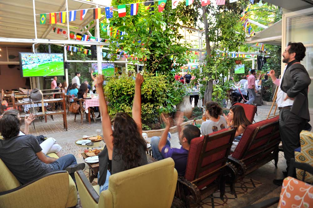 Football fans watch a World Cup game at Al Falamanki
