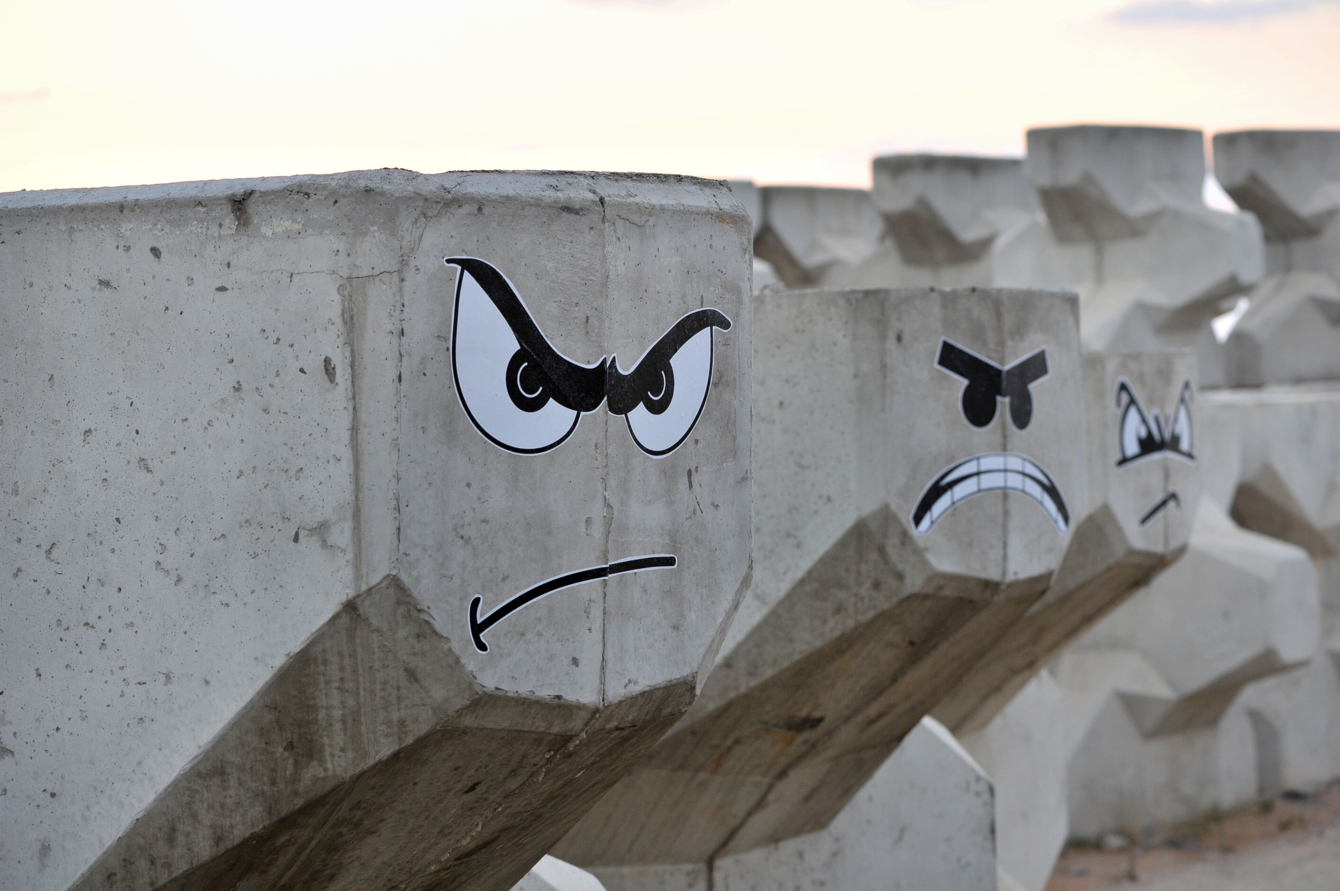 Angry faces are painted on port construction material.