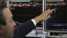 A trader from ETX Capital points to a Bloomberg terminal showing the FTSE 100 index following a speech by Finance minister George Osborne in central london on June 27, 2016. (Getty images)
